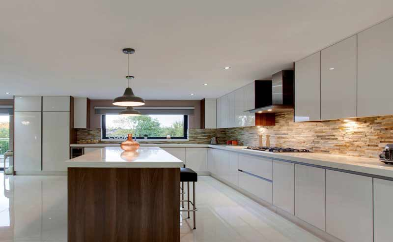 white modular kitchen in acrylics and blum fittings and island