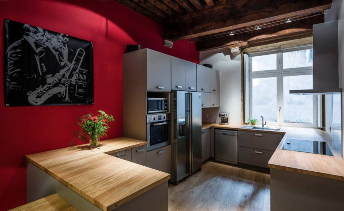 a red modular kichen with wooden countertop and inbuilt oven and micro in gurgaon